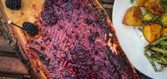 Gegrilde hele zalmzijde op Finse rookplank met bramensaus